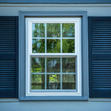 replacement window with dark blue shutters