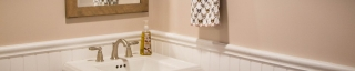 detail of pedestal sink and wainscoting on wall in remodeled bathroom