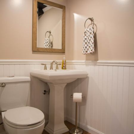 pedestal sink and toilet in remodeled bathroom with wainscoting molding
