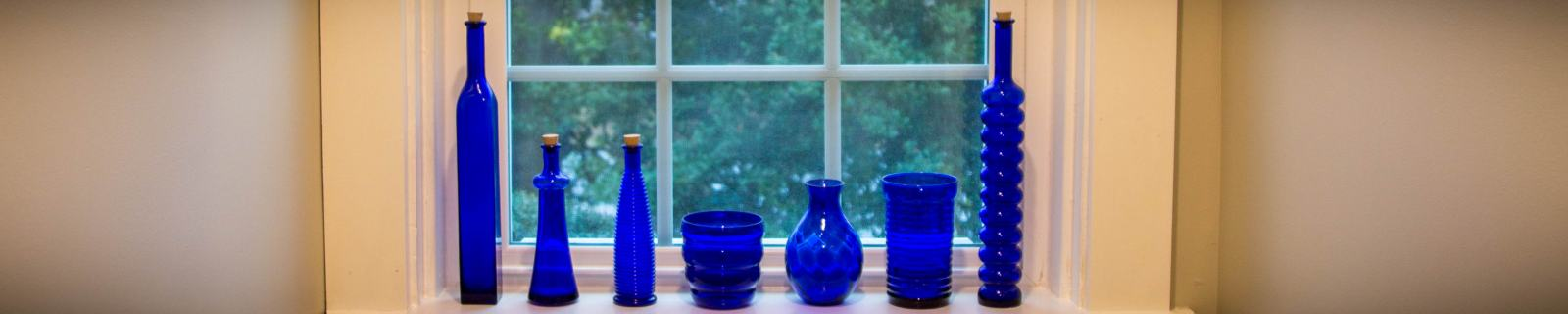 blue glass bottles along the sill of a replacement window in a remodeled bathroom