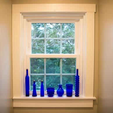 blue glass bottles along a window sill