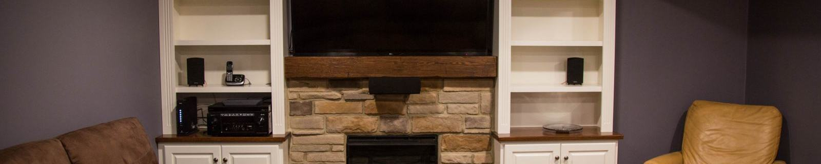 entertainment center with fireplace and built-in side shelving in finished basement