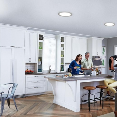 kitchen with sun tunnels in the ceiling and a family with a puppy