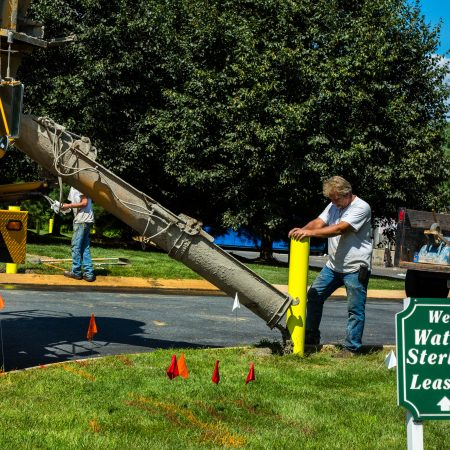 pouring concrete into base of gate post